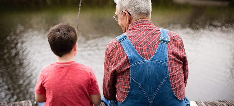 Grandfather and grandson sitting on a dock fishing